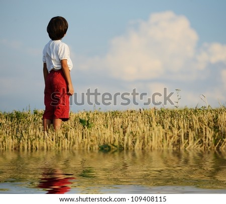 Kid standing on field alone