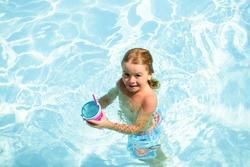 Kid swimming in pool. Children summer vacation. Summertime. Attractions concept. Swimmingpool