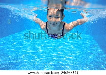 Kid swims in pool underwater, girl swimming, playing and having fun, children water sport
