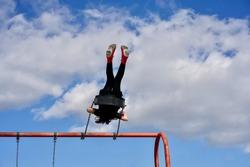 Kid swinging into the sky on playground swing