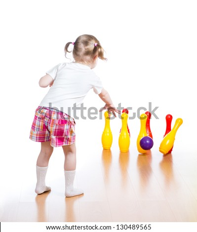 Kid throwing ball to knock down toy bowling pins. Focus on child girl standing back.
