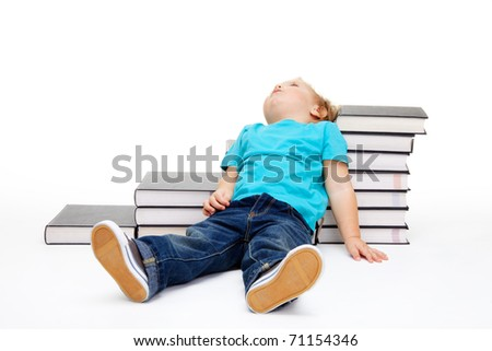 Kid tiered of education lay exhausted on the floor and steps made of books