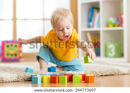 kid toddler playing  wooden toys at home or nursery
