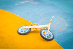 Kid toy bike abandoned and on the asphalt ground