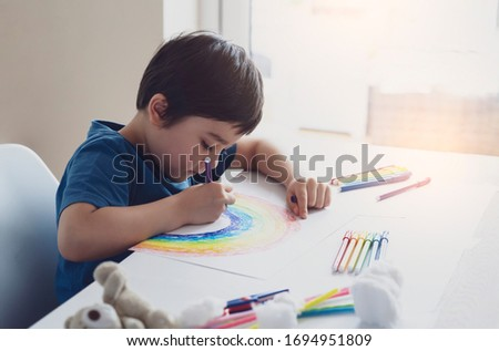 Kid using colour pen painting rainbow on paper,Child using digital tablet searching information on internet about rainbow color, Home schooling Social media campaign for coronavirus prevention concept