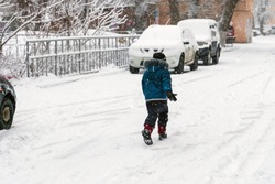 kid walking in the snow next to parked cars. Back view