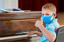 Kid wearing a mask and playing the piano at lesson and event. Kids back to school concept