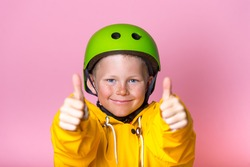 Kid with bright green protect helmet and sunglasses and yellow coat showing thumbs up. Funny face of blond freckled child boy. Extreme sport for children. Protect equipments for safety. Life insurance