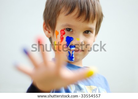 Kid with color on his fingers and face looking