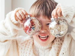Kid with decorative balls for Christmas tree.Boy in cable-knit oversized sweater.Cozy outfit for snuggle weather.Transparent balls with red, golden spangles inside.Winter holiday spirit.New year.