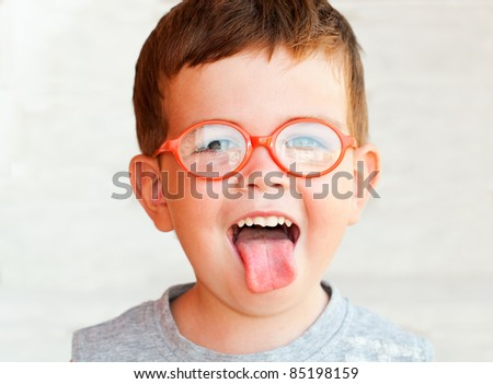 Kid with glasses showing his tongue