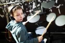 Kid with headphones playing drums in music class