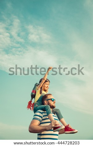 Kid with jet pack pretend to be superhero. Child playing with father in summer. Happy dad and son outdoors. Success, leader and winner concept #444728203