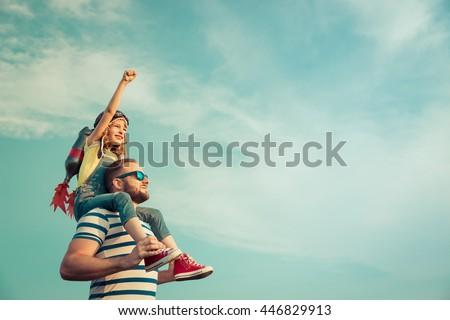 Kid with jet pack pretend to be superhero. Child playing with father in summer. Happy dad and son outdoors. Success, leader and winner concept