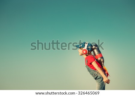 Kid with jetpack against autumn sky background. Child playing outdoors. Success, leader and winner concept. Retro toned