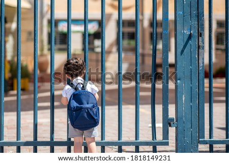 Kid with school backpack look on schoolyard towards an open entrance or exit door. Schools and preschools remain locked for children during lockdown, coronavirus pandemic and second wave of covid-19.