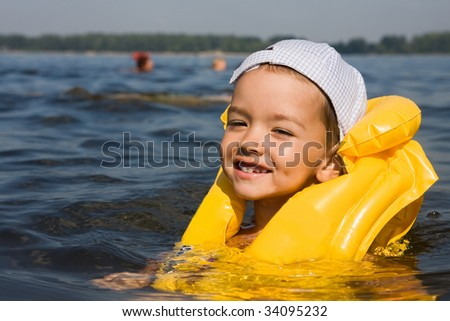 Kid with swimming vest in water