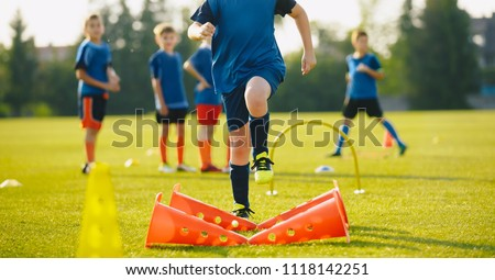 Kid Young Athletes Training with Football Equipment. Football Speed Training. Young Footballer in Blue Sportswear at Training Session on Grass Soccer Field