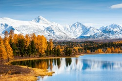 Kidelu lake, snow-covered mountains and autumn forest in Altai Republic, Siberia, Russia