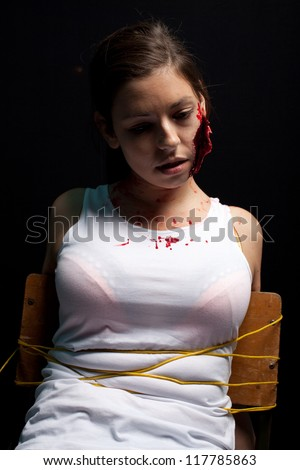 Kidnapped and tortured young woman with a big cut on her face, tied up