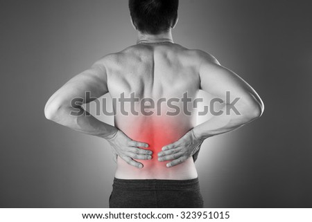 Kidney pain. Man with backache. Pain in the man\'s body. Black and white photo with red dot