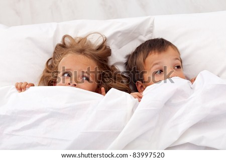 Kids afraid laying in bed and pulling the quilt on their heads