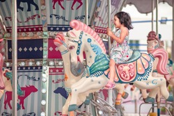 kids and Carousel . little girl is happy, enjoy playing the carousel horse During the weekend of family fun In the amusement park.