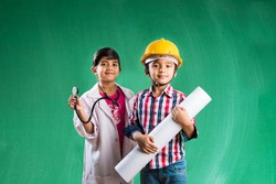 Kids and education concept - Small indian boy and girl posing in front of Green chalk board in engineers fancy dress and doctor costume with stethoscope