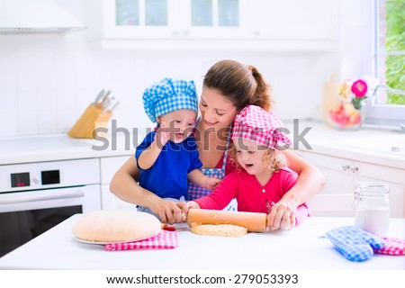 Kids and mother baking. Two children and parent cooking. Little girl and baby boy cook and bake in a white kitchen with modern oven. Brother and sister in chef hats making a pie for dinner.