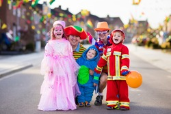 Kids and parents on Halloween trick or treat. Family in Halloween costumes with candy bags walking in decorated street trick or treating. Baby and preschooler celebrating carnival. Child costume.