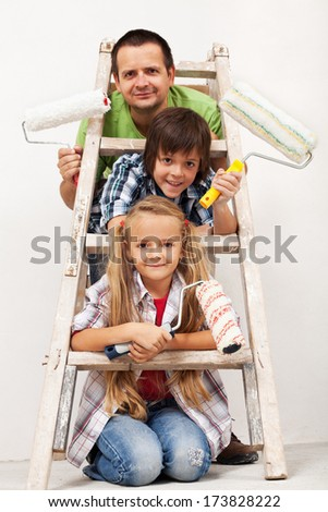Kids and their father getting ready to paint the room - equipped with paint roller and ladder