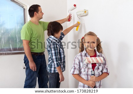 Kids and their father painting a room using paint roller - focus on girl in foreground