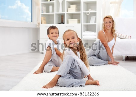 Kids and woman at home doing stretching yoga exercises - focus on the little girl