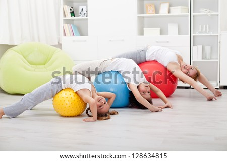 Kids and woman doing stretching exercises - using large balls
