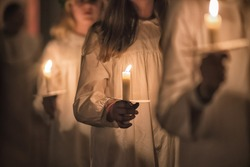 Kids are handling candles in the traditionall dresses. Celebration of Lucia day in Sweden