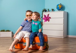 Kids are sitting on the big suitcase and ready to travel. Little child boy in sunglasses and girl with windmill hugging and laughing. Summer time holiday vacation.