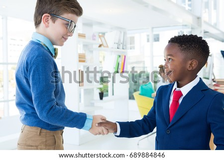 Kids as business executives shaking hands in office