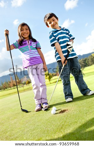 Kids at the course playing golf and looking happy