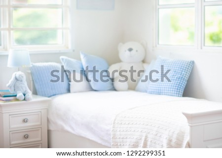 Kids bed in white sunny bedroom with window. Children room and interior design. Bed for baby or toddler boy at home. Bedding and textile for children nursery. Nap and sleep time.