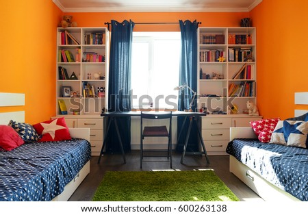 Kids bedroom in orange and blue colors with two beds and bookcases #600263138