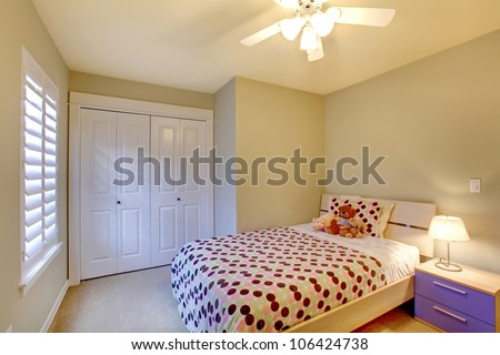Kids bedroom with minimal design and beige walls.