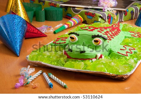 Kids birthday cake at party surrounded by presents and party hats