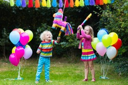 Kids birthday party. Group of children hitting pinata and playing with balloons. Family and friends celebrating birthday outdoors in decorated garden. Outdoor celebration with active games.