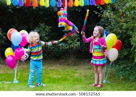 Kids birthday party. Group of children hitting pinata and playing with balloons. Family and friends celebrating birthday outdoors in decorated garden. Outdoor celebration with active games. #508152565