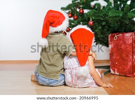 Kids boy and girl looking at the christmas tree hugging stock