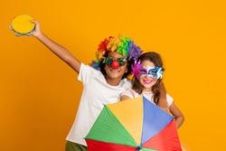 kids celebrating Carnival together at yellow background. Two children celebrating carnival in brazil.