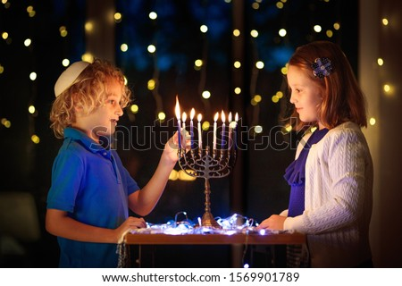 Kids celebrating Hanukkah. Jewish festival of lights. Children lighting candles on traditional menorah. Boy in kippah with dreidel and Sufganiyah doughnut. Israel holiday. ストックフォト ©