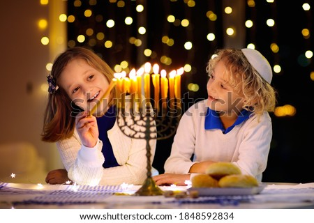 Kids celebrating Hanukkah. Jewish festival of lights. Children lighting candles on traditional menorah. Boy in kippah with dreidel and Sufganiyah doughnut. Israel holiday. Сток-фото ©