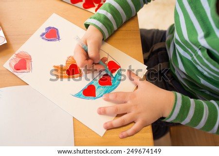 Kids, children, doing Valentine\'s day arts and crafts with hearts, pencils, paper