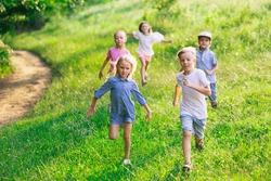 Kids, children running on meadow, summertime